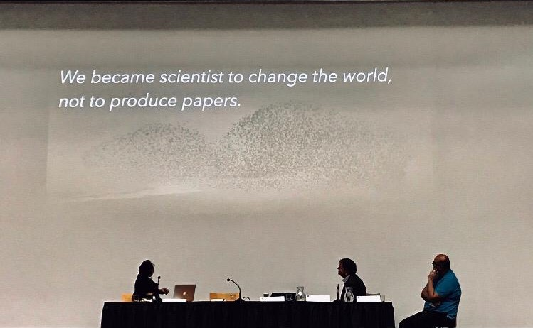 "A powerpoint slide with the words ""We became scientists to change the world, not to produce papers"" The speakers sit in the foreground."